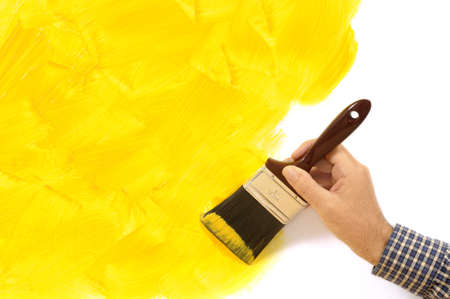 decoration messy: Man holding a paintbrush with a partly finished blank yellow painted wall.  Space for copy.