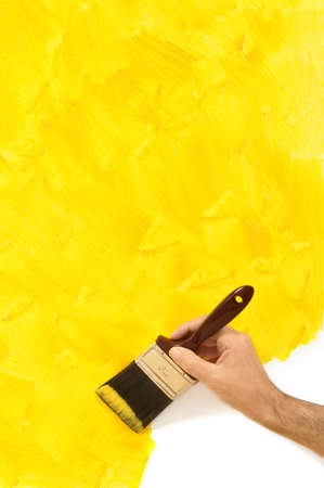 brushstrokes: Man holding a paintbrush with a partly finished blank yellow painted wall.  Space for copy.