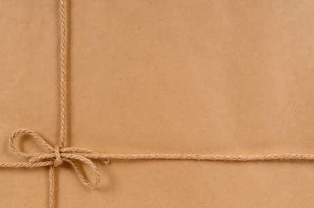 mail order: Background of brown paper package tied with natural rope.