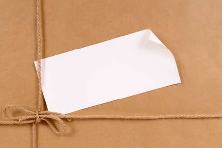 shipped: Background of brown paper package with curled corner label. Stock Photo