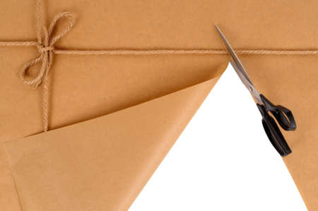 unwrapping: Brown paper package being cut by scissors Stock Photo