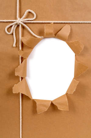 unwrapping: Brown paper package with untidy torn hole
