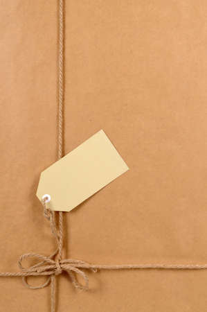 mail order: Background of brown paper package with untidy tied label or gift tag.