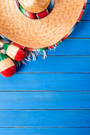 celebration background: Mexican sombrero and maracas with traditional serape blanket laid on an old blue painted pine wood floor.  Space for copy. Stock Photo