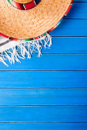 serape: Mexican sombrero with traditional serape blanket laid on an old blue painted pine wood floor.  Space for copy.