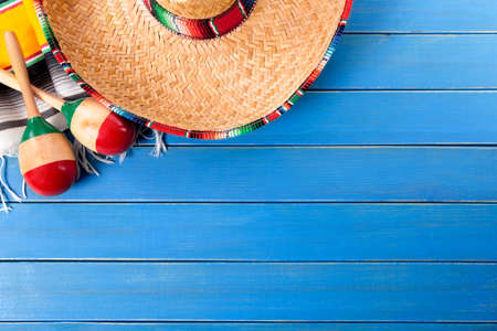 Mexican sombrero and maracas with traditional serape blanket laid on an old blue painted pine wood floor.  Space for copy. photo