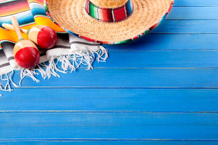 mayo: Mexican sombrero and maracas with traditional serape blanket laid on an old blue painted pine wood floor.  Space for copy. Stock Photo