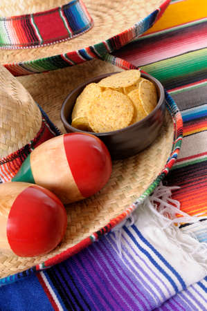 serape: Mexican sombreros and traditional serape blankets with maracas and tortilla chips.