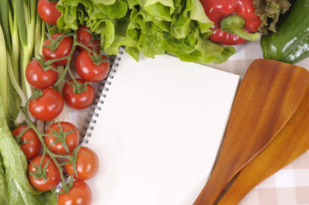 Selection of salad vegetables with blank recipe book or shopping list on a check tablecloth. photo