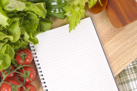 Selection of salad vegetables with blank recipe book or shopping list on a green check tablecloth with wood chopping board. photo