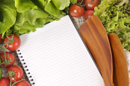 Selection of salad vegetables with blank recipe book or shopping list and wooden serving spoons. photo