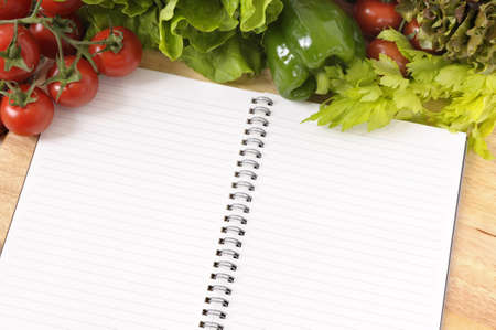 Selection of salad vegetables with blank recipe book or shopping list on a wood chopping board. photo
