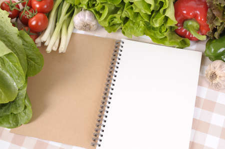 Selection of salad vegetables with blank recipe book or notebook on a check tablecloth. photo