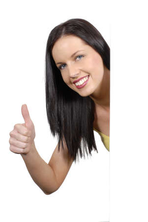 thumbsup: Woman giving thumb up sign from a plain white board.  Space for copy.