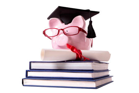 Pink piggy bank dressed as a college graduate with mortar board, glasses and diploma standing on a small stack of books.  Isolated on white. photo