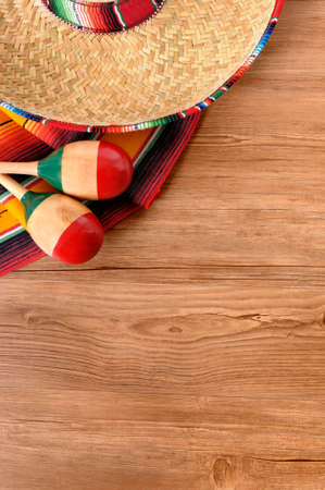 serape: Mexican background with sombrero straw hat, maracas and traditional serape blanket or rug on a wood floor.  Space for copy. Stock Photo