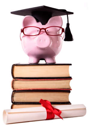 Pink piggy bank dressed as a college student with mortar board, glasses and diploma standing on a stack of old textbooks.  Isolated on white.  Diploma is out of focus in foreground. photo