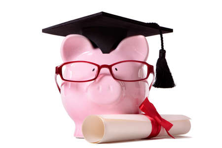 Pink piggy bank dressed as a college graduate with mortar board, diploma and glasses.  Isolated on white. photo