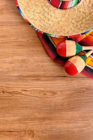 Mexican background with sombrero straw hat, maracas and traditional serape blanket or rug on a wood floor.  Space for copy. Banco de Imagens