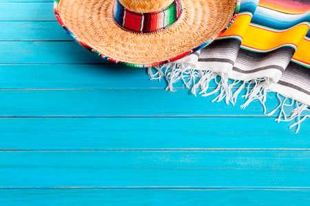 Sombrero mexicain et couverture de serape traditionnelle posé sur un vieux plancher de bois peint de pin bleu. Espace pour la copie. Banque d'images - 38366937