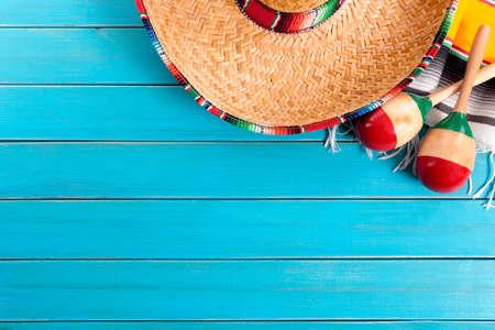 メキシコのソンブレロと伝統的なセラーベ毛布にマラカスは、古い青い塗られた松の木の床に置いた。 コピーのためのスペース。 写真素材