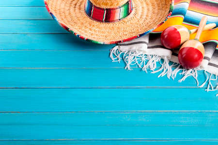 Mexican sombrero and maracas with traditional serape blanket laid on an old blue painted pine wood floor.  Space for copy. Stock Photo