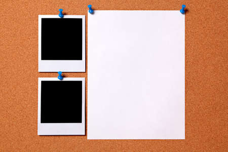 pinned: Blank photo prints and plain paper poster pinned to a cork notice board.  Space for copy.  Pathe provided. Stock Photo