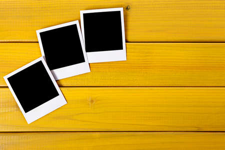provided: Three blank photo prints on a wood desk or table.  Space for copy.  Paths provided. Stock Photo