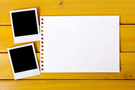 Two blank photo prints on a wood desk or table with a page torn from a spiral notebook.  Space for copy.  Paths provided.