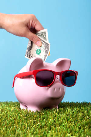 Hand putting a one dollar bill into a pink piggy bank wearing sunglasses.