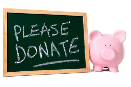 charity collection: Piggy bank standing by a blackboard with charity donation message.  Isolated on white.