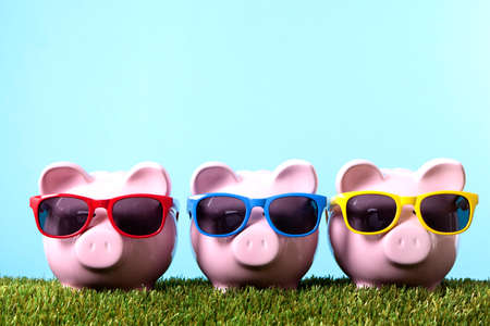 Three pink piggy banks with sunglasses on grass with blue sky Archivio Fotografico