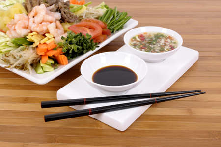 korean food: Selection of asian vegetables with peeled prawns, soy sauce, chilli dip and chopsticks Stock Photo