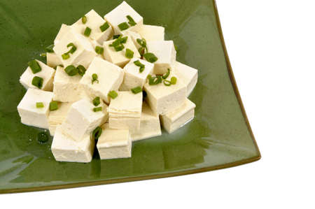 cubed: Cubes of fresh tofu garnished with spring onion slices on a green plate fully isolated on white