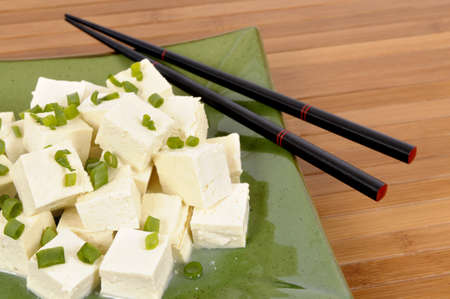 bean curd: Cubes of fresh tofu garnished with spring onion slices on a green plate and bamboo background.