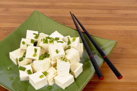 bean curd: Cubes of fresh tofu garnished with spring onion slices, with chopsticks and bamboo background.