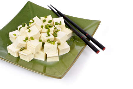 bean curd: Cubes of fresh tofu garnished with spring onion slices on a green plate with white background.