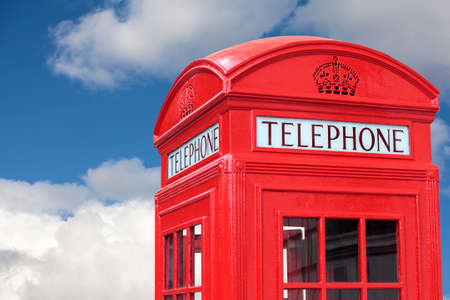 telephone box: London traditional red telephone box isolated against a blue cloudy sky