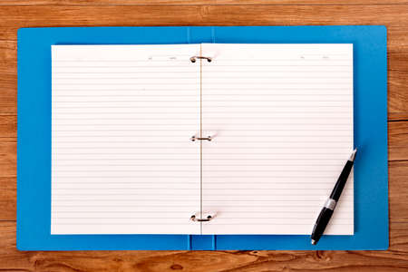 ring binder: Students desk with blue project folder and ballpoint pen. Stock Photo