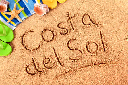del: The words Costa del Sol written on a sandy beach with beach towel, starfish and flip flops.