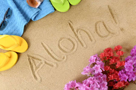 hawaiian lei: The word Aloha written in soft sand with flip flops, flowers and beach towel