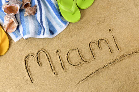 The word Miami written in sand with flip flops and beach towel. Stock Photo