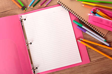 Busy student's desk with pink project folder surrounded by pens, pencils and notebooks.