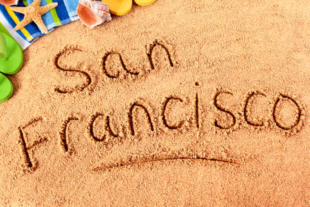 The words San Francisco written on a sandy beach with beach towel, starfish and flip flops. photo