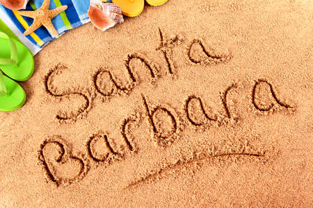 The words Santa Barbara written on a sandy beach wih beach towel, starfish and flip flops.