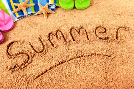 The word Summer written on a sandy beach, with towel, starfish and flip flops. photo