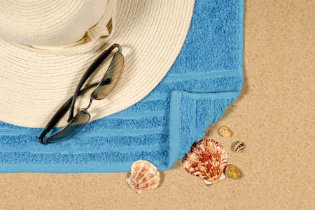 beach towel: Seashore background with straw hat beach towel and sunglasses.