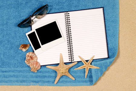 Beach scene with blank writing book and  photo prints photo