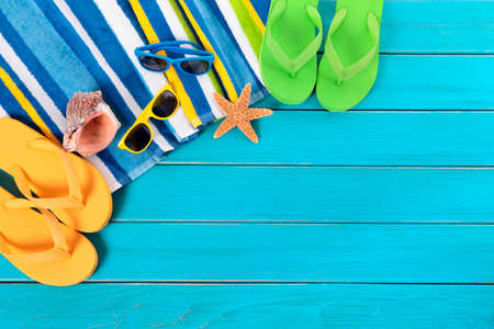 flops: Beach scene with striped towel, sunglasses, flip flops, seashell and starfish laid on old weathered blue wood decking.  Space for copy.