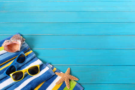 decking: Beach scene with striped towel, sunglasses, starfish and seashell on old weathered blue painted wood decking.  Space for copy.